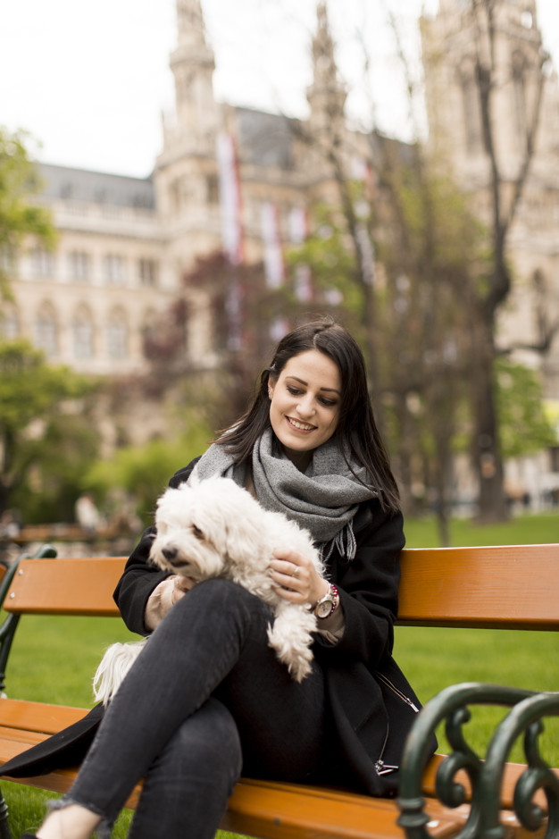Young woman sitting in the park and holding a small dog in her l